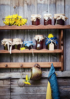 Jars of dandelion syrup on wooden shelves