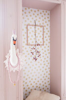 Felt swan's head on wall next to niche with flowering twig in frame on wall