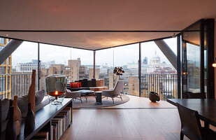 Modern living room with panoramic city view through glass walls