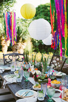 Lanterns above table set in bright colours for Mexican party