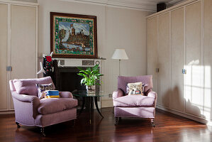 Two lilac armchairs in front of open fireplace and next to cupboard