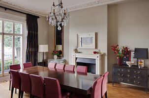 Pink upholstered chairs at long table in classic dining room with fireplace