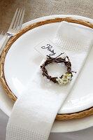 Gedeck mit weißer Stoffserviette und Weidenkränzchen mit Frühlingsblüten