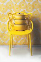 Saucepans stacked on yellow designer chair against yellow and white wallpaper