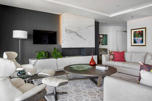 Helle Polstermöbel, Ledersesssel und Kamin in Marmorausführung in elegantem Wohnzimmer