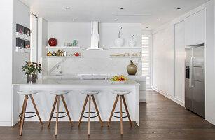 Weiße, offene Küche mit Theke und Barhockern