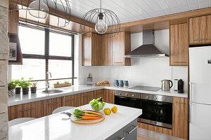 Gemüse auf der Kücheninsel in moderner Küche mit Holzfronten