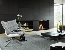 Designer armchair in front of black fitted cupboards in living room