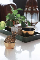 Pineapple ornament in golden bowl in front of Chinese money plant on tray