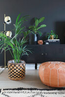 Leather pouffe, potted palm and console table against black wall