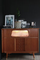 Pictures and cactus on top of 50s cabinet