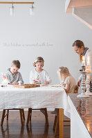 Kinder beim Plätzchenverzieren am Tisch