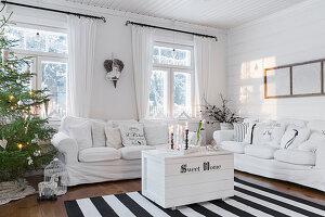 Weiße Couchgarnitur, Truhe als Couchtisch und Weihnachtsbaum im Wohnzimmer