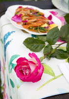 A pink rose and sautéed chicken with peperoni and rose petals on a garden table