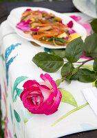 Pinkfarbene Rose und sautiertes Hähnchen mit Peperoni und Rosenblättern auf Gartentisch