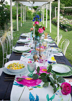 A laid table decorated with roses under a pergola