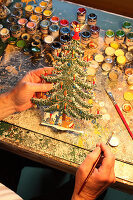 Hand-painted pewter Christmas tree in workshop