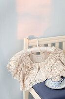 Lace bolero and pearl necklace in teacup on chair