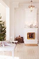 Kachelofen mit brennendem Feuer und geschmückter Weihnachtsbaum in offenem Wohnraum