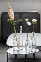 Vases made from various cut-off bottles on side table