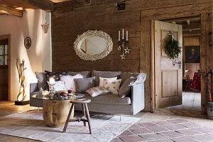 Grey sofa with scatter cushions, table with round glass top and wooden stools in rustic cabin
