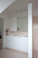 Simple white cabinets and washstand in bathroom with mosaic tiles