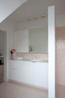 Schlichte, weiße Einrichtung mit Waschtischunterschrank im Badezimmer mit Mosaikfliesen