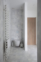 Handtuchtrockner und Blick auf Toilette mit Trennwand im Badezimmer