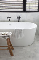Free-standing bathtub and wooden stool below window