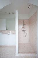 Tiled shower area in simple bathroom with white fittings