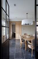 Holztisch und Polsterstühle in elegantem Esszimmer mit Naturstienfliesen