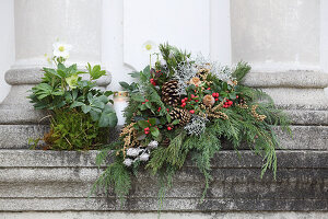 Grave arrangement of conifer twigs, hellebores, Gaultheria berries, pine cones and silver ragweed