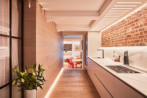 Long, narrow kitchen with brick wall leading into dining room