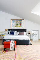 Double bed with designer chair used as bedside table and red pouffe on patterned rug in bedroom