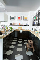 U-shaped fitted kitchen with black base cabinets and wooden worksurface