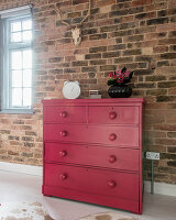 Old chest of drawers painted hot pink against brick wall