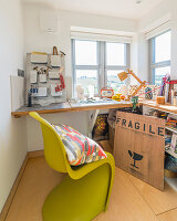 Green designer chair at L-shaped desk below windows