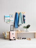 Garderobe und Holzbank an grauer Bretterwand im Flur