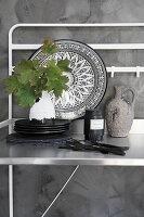Metallgstell mit Tellern und Vase mit Blätterzweig