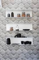 Wandregale mit Vorratsgläsern, Geschirr un Vasen an tapezierter Wand