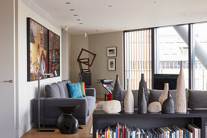 Vases on top of bookcase in front of lounge with grey upholstered furniture