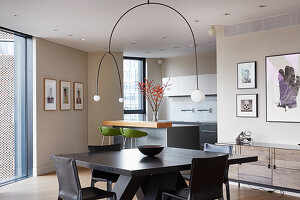 Designer lamp above dining table and chairs in open-plan interior with fitted kitchen in background