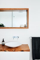Designer sink on washstand with wooden top below wood-clad niche with mirror on back wall