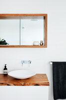 Designer-Waschschüssel auf Waschtisch mit Holzplatte, darüber Wandnische mit Holzrahmen und Spiegel