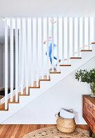 Treppe mit Geländer aus weißen Stelen, Sideboard mit Blätterzweig und Korbtasche auf dem Boden