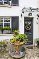 Holztisch mit Pflanzen und Gießkannen vor Hauseingang
