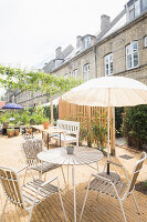 Sunny seating area in courtyard behind old terrace houses