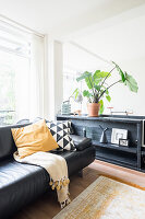 Black leather sofa next to half-height cabinet in bright living room