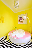 Round bed and standard lamp in bedroom with yellow walls and lack-and-white striped carpet