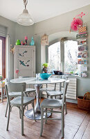 Round table, wooden chairs and corner cupboard in kitchen